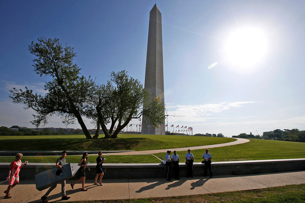 . Steven Avila, a Department of Interior employee, left, carries a Washington Monument costume as he arrives at the Washington Monument in Washington, Monday, May 12, 2014, ahead of a ceremony to celebrate its re-opening. The monument, which sustained damage from an earthquake in August 2011, is reopening to the public today. Avila made the costume to show his support for the re-opening of the monument. (AP Photo)