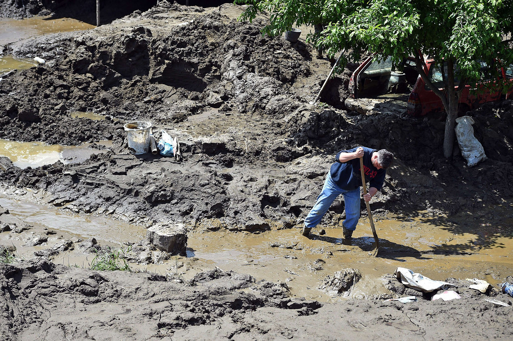 Description of . A man clears mud from his front yard in  Krupanj, some 130 kilometers south west of Belgrade, on May 20, 2014, after it was hit with floods and landslides, cutting the western Serbian town off for four days. Serbia declared three days of national mourning on May 20 as the death toll from the worst flood to hit the Balkans in living memory rose and health officials warned of a possible epidemic. At least 49 people have been killed already by the worst floods in central Europe for a century and more than 1.6 million people have been hit as the river Sava and its tributaries have burst their banks, inundating tens of thousands of hectares of farmland and destroying houses and buildings.   AFP PHOTO / ANDREJ ISAKOVIC/AFP/Getty Images