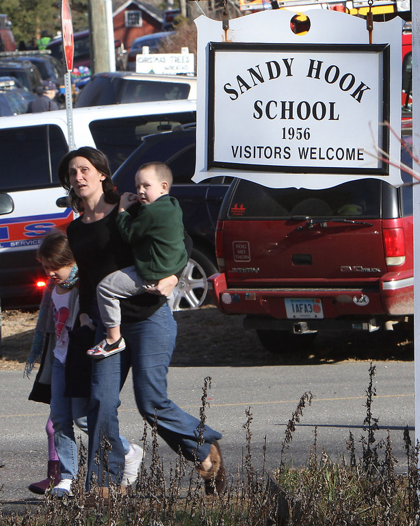 Description of . A parent walks away from the Sandy Hook Elementary School with her children following a shooting at the school in Newtown, Conn. on Friday, Dec. 14, 2012. (AP Photo/The Journal News, Frank Becerra Jr.)
