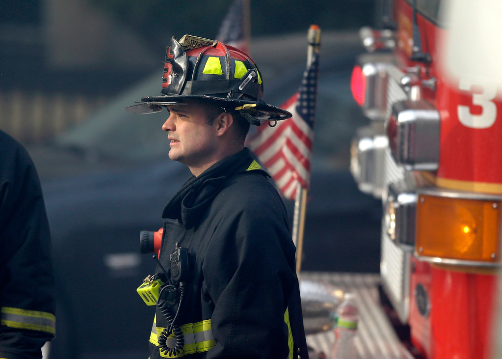 Description of . A firefighter looks on at the scene of a multi-alarm fire at a four-story brownstone in the Back Bay neighborhood near the Charles River, Wednesday, March 26, 2014, in Boston.  (AP Photo/Steven Senne)