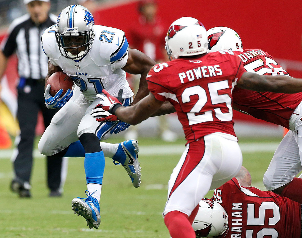 Description of . Detroit Lions running back Reggie Bush (21) gains yards as Arizona Cardinals inside linebacker Karlos Dansby (56) John Abraham (55) and Jerraud Powers (25) defend during the first half of a NFL football game, Sunday, Sept. 15, 2013, in Glendale, Ariz. (AP Photo/Darryl Webb)