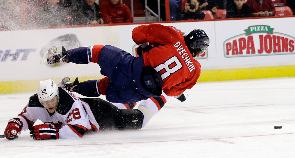 Description of . Washington Capitals left wing Alex Ovechkin (8), of Russia, loses the puck as he falls over New Jersey Devils defenseman Anton Volchenkov (28), also of Russia, in the second period of an NHL hockey game, Thursday, Feb. 21, 2013 in Washington. The Devils won 3-2. (AP Photo/Alex Brandon)