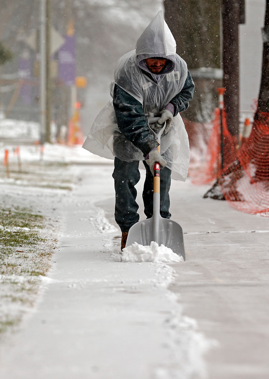 Description of . Steven Cervantes shovels away the snow from a sidewalk as a winter storm moves into the area Wednesday, Feb. 12, 2014, in Charlotte, N.C. (AP Photo/Chuck Burton)