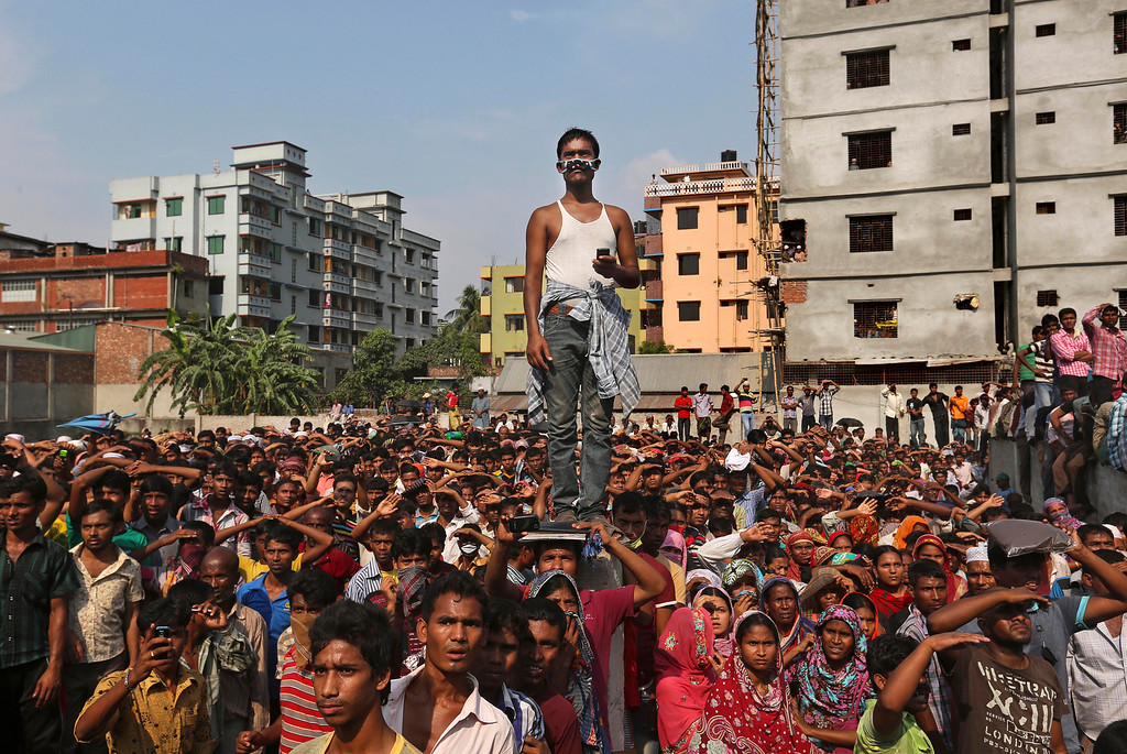 Description of . Bangladeshis watch the rescue operations at the site of a building that collapsed Wednesday in Savar, near Dhaka, Bangladesh, Thursday, April 25, 2013.  (AP Photo/Kevin Frayer)