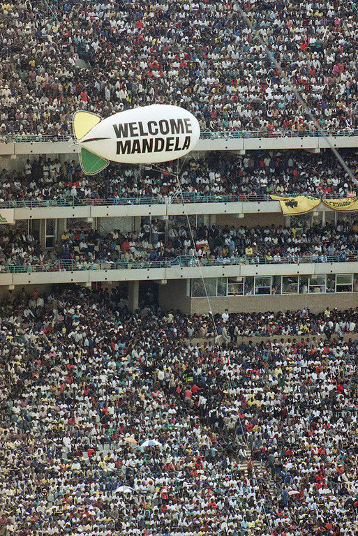 Description of . A balloon bearing a welcome sign for Nelson Mandela airborne over Soweto's Soccer City stadium, where the recently released ANC leader addressed the crowd of 120,000 packed into the venue, Tuesday, Feb. 13, 1990. Mandela was released from prison after serving over 27 years. (AP Photo/Sean Woods)