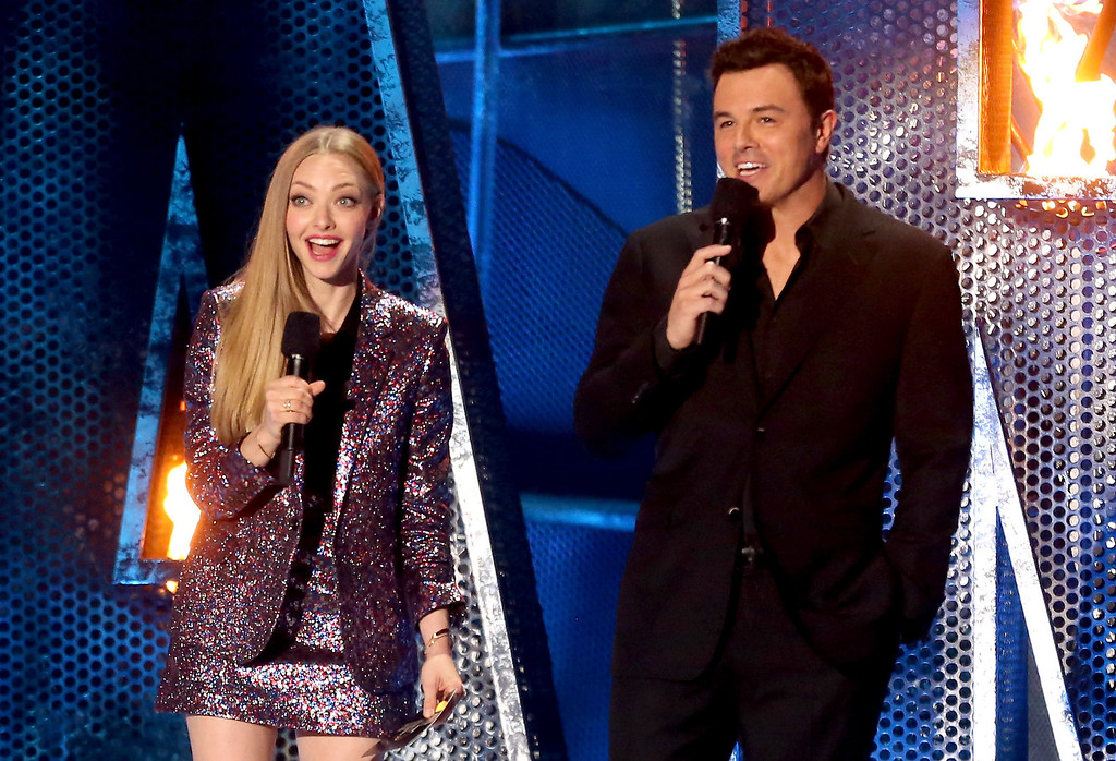 Description of . Actors Amanda Seyfried (L) and Seth MacFarlane speak onstage at the 2014 MTV Movie Awards at Nokia Theatre L.A. Live on April 13, 2014 in Los Angeles, California.  (Photo by Frederick M. Brown/Getty Images)