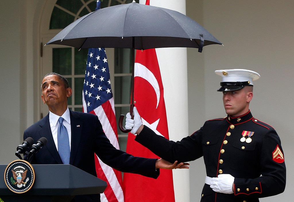 Description of . President Barack Obama looks to see if it is still raining as a Marine holds an umbrella for him during his joint news conference with Turkish Prime Minister Recep Tayyip Erdogan, not pictured, Thursday, May 16, 2013, in the Rose Garden of the White House in Washington. (AP Photo/Charles Dharapak)