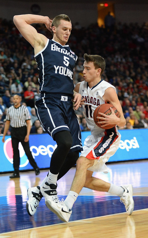 Description of . David Stockton #11 of the Gonzaga Bulldogs drives against Kyle Collinsworth #5 of the Brigham Young Cougars during the championship game of the West Coast Conference Basketball tournament at the Orleans Arena on March 11, 2014 in Las Vegas, Nevada.  (Photo by Ethan Miller/Getty Images)