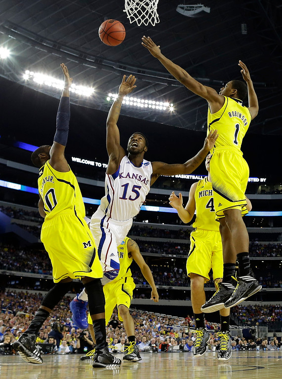Description of . Kansas\' Elijah Johnson (15) shoots in traffic during the first half of a regional semifinal game against the Michigan in the NCAA college basketball tournament, Friday, March 29, 2013, in Arlington, Texas.  (AP Photo/David J. Phillip)