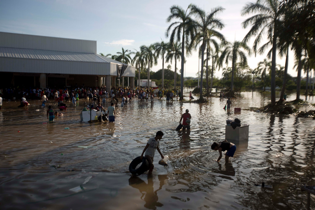 Description of . People wade through waist-high water in a store's parking, looking for valuables, south of Acapulco, in Punta Diamante, Mexico, Wednesday, Sept. 18, 2013. Mexico was hit by the one-two punch of twin storms over the weekend, and the storm that soaked Acapulco on Sunday - Manuel -re-formed into a tropical storm Wednesday, threatening to bring more flooding to the country's northern coast. With roads blocked by landslides, rockslides, floods and collapsed bridges, Acapulco was cut off from road transport. (AP Photo/Eduardo Verdugo)