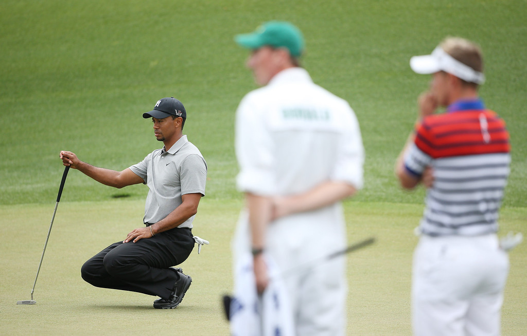 Description of . Tiger Woods of the United States lines up a putt on the the eighth green as Luke Donald of England looks on during the first round of the 2013 Masters Tournament at Augusta National Golf Club on April 11, 2013 in Augusta, Georgia.  (Photo by Andrew Redington/Getty Images)