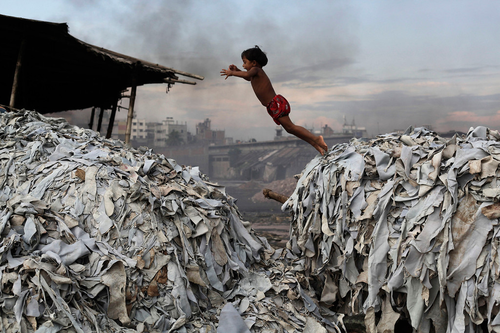Description of . A child jumps on the waste products that are used to make poultry feed as she plays in a tannery at Hazaribagh in Dhaka October 9, 2012. Luxury leather goods sold across the world are produced in a slum area of Bangladesh's capital where workers, including children, are exposed to hazardous chemicals and often injured in horrific accidents, according to a study released on Tuesday. None of the tanneries packed cheek by jowl into Dhaka's Hazaribagh neighborhood treat their waste water, which contains animal flesh, sulphuric acid, chromium and lead, leaving it to spew into open gutters and eventually the city's main river. REUTERS/Andrew Biraj