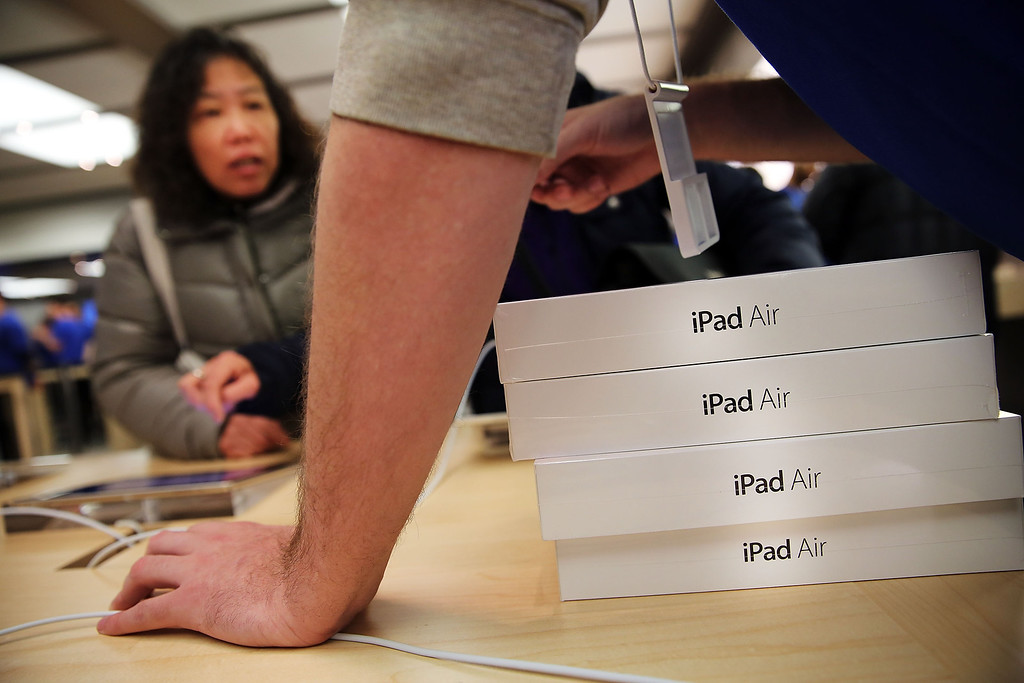 Description of . Apple employees sell the new iPad Air at the Apple Store on November 1, 2013 in New York City.   (Photo by Spencer Platt/Getty Images)