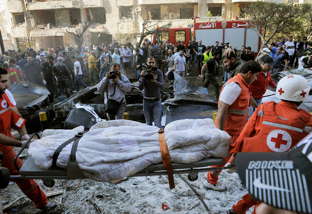 Description of . Lebanese Red Cross members carry a blanket-wrapped body at the site of explosions near the Iranian embassy in Beirut, Lebanon, 19 November 2013. reports vary regarding fatalities but at least 15 people are believed to have been killed in south Beirut, a stronghold of the Hezbollah militant movement  EPA/WAEL HAMZEH