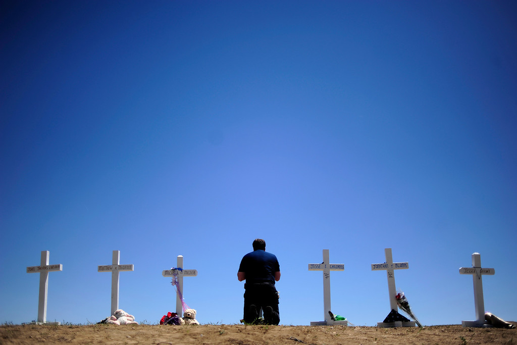 Description of . Travis Hirko kneels at the cross of Alex Sulliven at a memorial for the victims of the Aurora Theater Shooting at the intersection of Sable Boulevard and Centerpoint Drive on Sunday, July 22, 2012. AAron Ontiveroz, The Denver Post