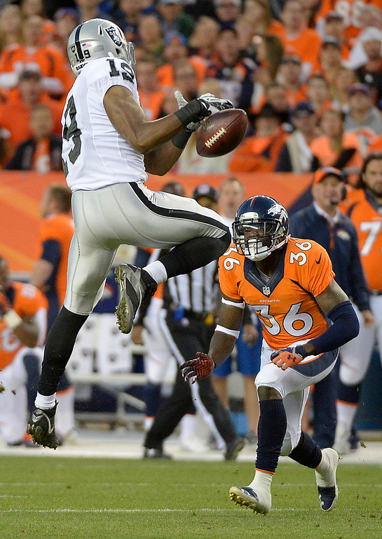 Description of . Oakland Raiders wide receiver Jacoby Ford (12) drops a pass as Denver Broncos cornerback Kayvon Webster (36) closes in for a tackle in the first quarter. The Denver Broncos took on the Oakland Raiders at Sports Authority Field at Mile High in Denver on September 23, 2013. (Photo by John Leyba/The Denver Post)