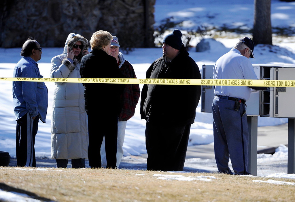 Description of . A mailman sorts out mail at a mailbox as onlookers stand nearby a crime scene at 16005 Ithaca Place in Aurora Saturday afternoon. The bodies of four people, including a gunman are dead at the scene following a standoff situation early Saturday morning. The Denver Post/ Andy Cross