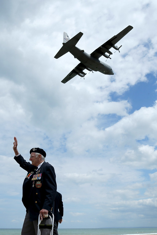 Description of . Former Royal Engineer and D-Day veteran Gordon Smith, aged 90, from Newbury, waves as a military aircraft passes overhead after the Royal Artillery Commemoration Service and parade at Sword Beach on June 5, 2014 in Hermanville, France.   (Photo by Christopher Furlong/Getty Images)
