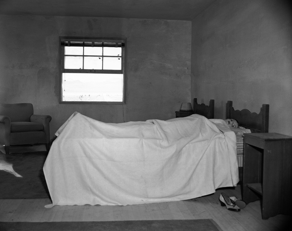 Description of . Stretched on a bed, in an upstairs bedroom of house number two, is a mannequin ready to test the effects of an atomic explosion at the atomic proving grounds near Las Vegas, Nev., March 15, 1953. Thorough the window a mile and a half away stands a 300 foot steel tower atop which the bomb will be detonated. The purpose of the test blast is to show Civil Defense officials what would happen in an American city if it were subjects to a atomic attack. (AP Photo/Dick Strobel)