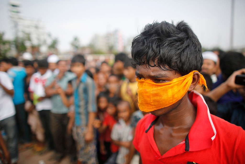 Description of . A boy covers his nose with a cloth as people gather in front of mass graves during the burial of unidentified garment workers, who died in the collapse of the Rana Plaza building in Savar, in Dhaka May 1, 2013. The European Union is considering trade action against Bangladesh, which has preferential access to EU markets for its garments, in order to pressure Dhaka to improve safety standards after the building collapse killed hundreds of factory workers. REUTERS/Andrew Biraj
