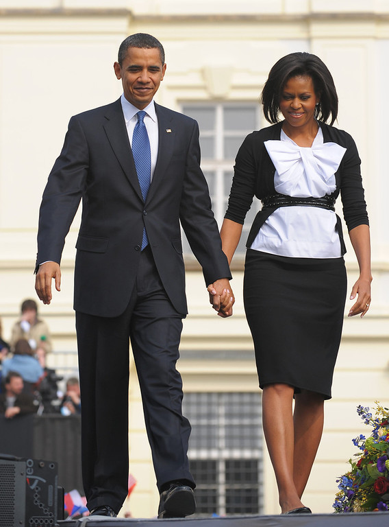 Description of . US President Barack Obama and First Lady Michelle Obama join hands April 05, 2009 as they walk away from the stage following an address at Hradcany Square in Prague. Barack Obama pledged Sunday to lead the quest for a world without nuclear weapons, denouncing