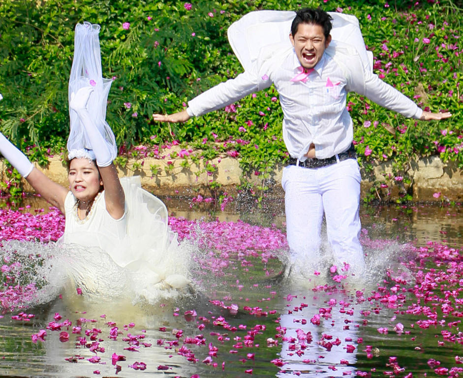 . Varutton Rangsitwong, left, and Prasit Rangsitwong jump into the water during a part of an adventure-themed wedding ceremony in Prachinburi province, Thailand, Wednesday, Feb. 13, 2013, on the eve of Valentine\'s Day. Three couples participated in the ceremony. (AP Photo/Wason Wanichakorn)