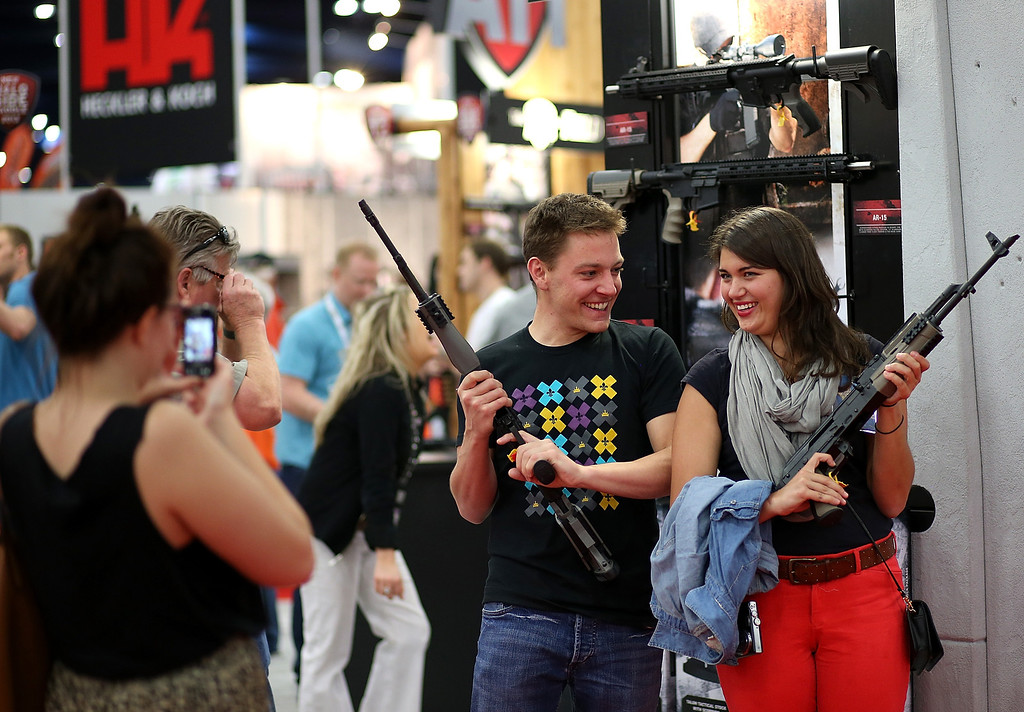 Description of . HOUSTON, TX - MAY 04:  Attendees hold assault rifles as they pose for a photo during the 2013 NRA Annual Meeting and Exhibits at the George R. Brown Convention Center on May 4, 2013 in Houston, Texas.  More than 70,000 people are expected to attend the NRA's 3-day annual meeting that features nearly 550 exhibitors, gun trade show and a political rally. The Show runs from May 3-5.  (Photo by Justin Sullivan/Getty Images)