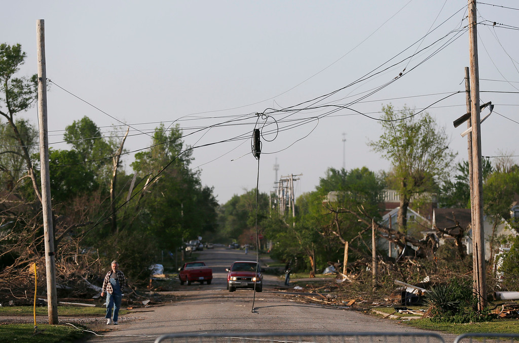 Description of . A resident walks under damaged power lines after a tornado in Baxter Springs, Kan., Monday, April 28, 2014. Sunday's tornado injured 25 people and damaged dozens of buildings. (AP Photo/Orlin Wagner)