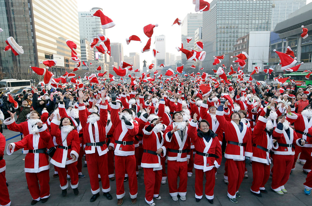 Description of . More than 1,000 volunteers clad in Santa Claus costumes throw their hats in the air as they gather to deliver gifts for the poor in downtown Seoul, South Korea, Tuesday, Dec. 24, 2013. (AP Photo/Lee Jin-man)