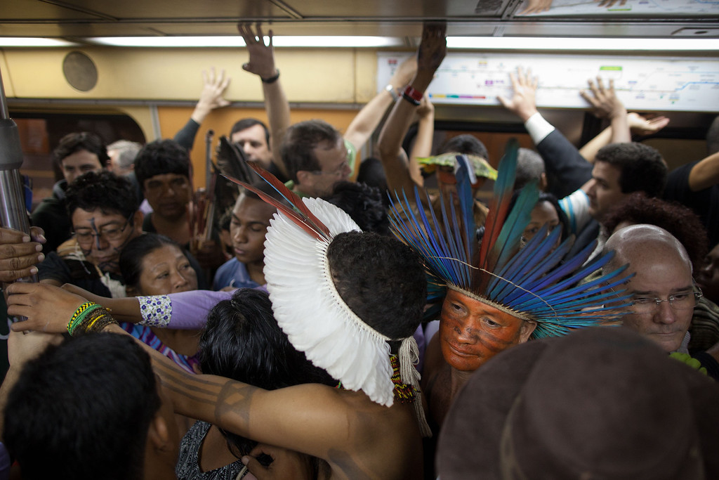Description of . In this June 18, 2012 file photo, Indigenous squeeze into a subway train as they ride to the People's Summit for Social and Environmental Justice in defense of the commons, a parallel event taking place alongside the United Nations Conference on Sustainable Development, or Rio+20, in Rio de Janeiro, Brazil. The Earth summit ran through June 22, with three final days of high-profile talks among some 130 top leaders from nations around the globe. (AP Photo/Felipe Dana, File)