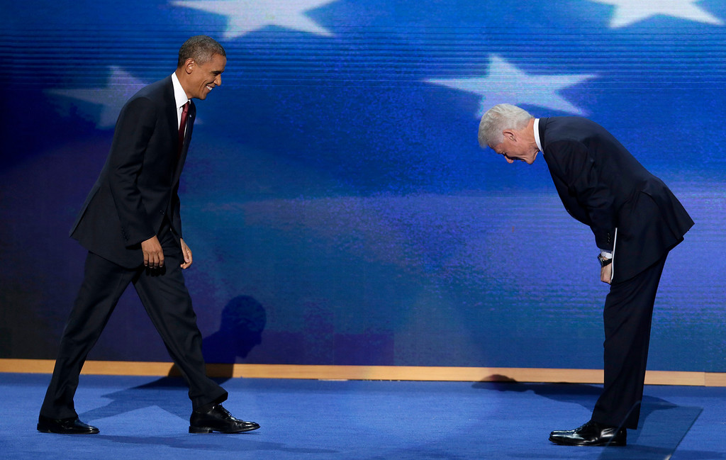 Description of . In this Sept. 5, 2012 file photo, former President Bill Clinton bows as President Barack Obama walks on stage after Clinton's address to the Democratic National Convention in Charlotte, N.C. (AP Photo/J. Scott Applewhite, File)