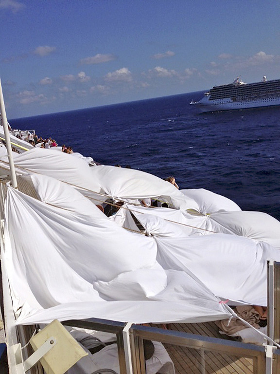 Description of . This Sunday, Feb. 10, 2013 photo, provided by Kalin Hill, of Houston, shows passengers with makeshift tents on the the deck of the Carnival Triumph cruise ship at sea in the Gulf of Mexico. The ship nearing Mobile Bay is without engine power and is being towed by tugboats. (AP Photo/Kalin Hill)