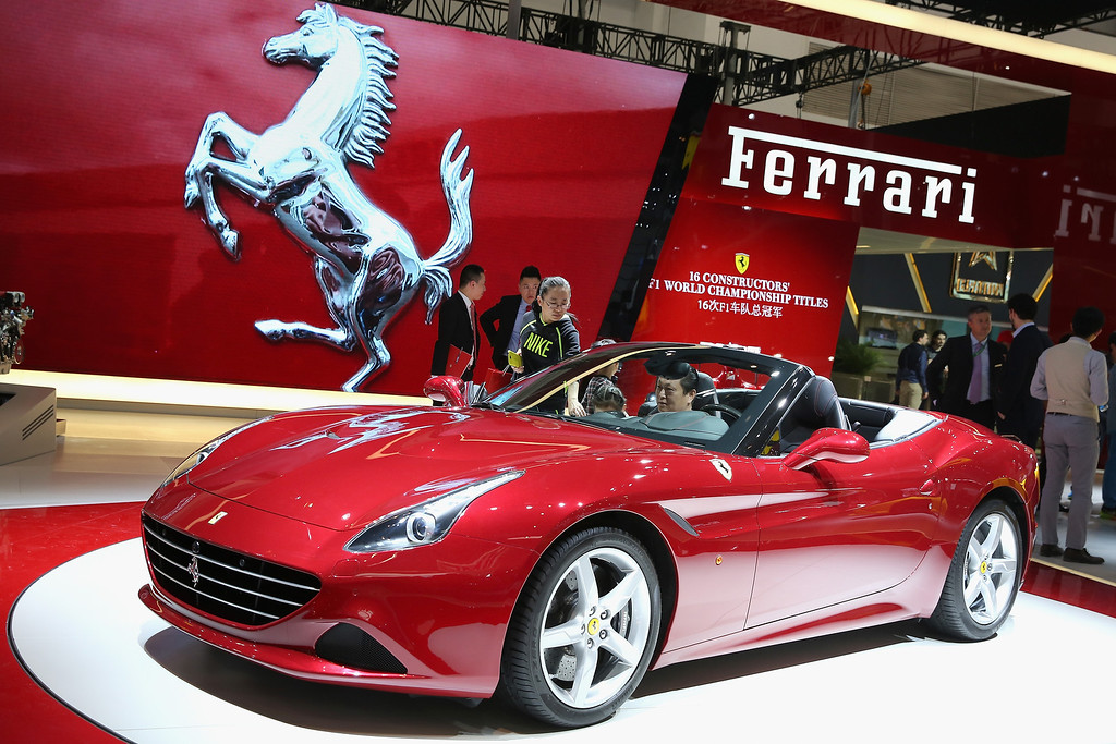 Description of . The potential consumers look at a Ferrairi sport car during the 2014 Beijing International Automotive Exhibition at China International Exhibition Center on April 21, 2014 in Beijing, China. More than 2,000 automotive enterprises from 14 countries and regions participated in the 2014 Beijing International Automotive Exhibition from April 20 to April 29.  (Photo by Feng Li/Getty Images)