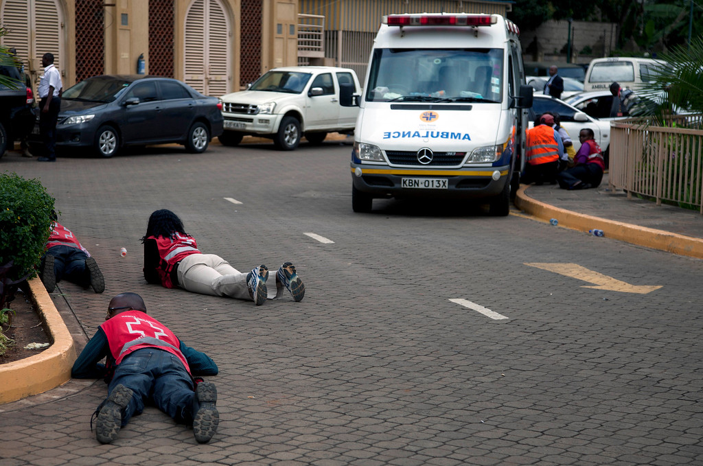 Description of . Red Cross Paramedics lie down beside a parked ambulance outside the Westgate Mall in Nairobi after heavy shooting started again on Monday, Sept. 23, 2013.  (AP Photo/Sayyid Azim)