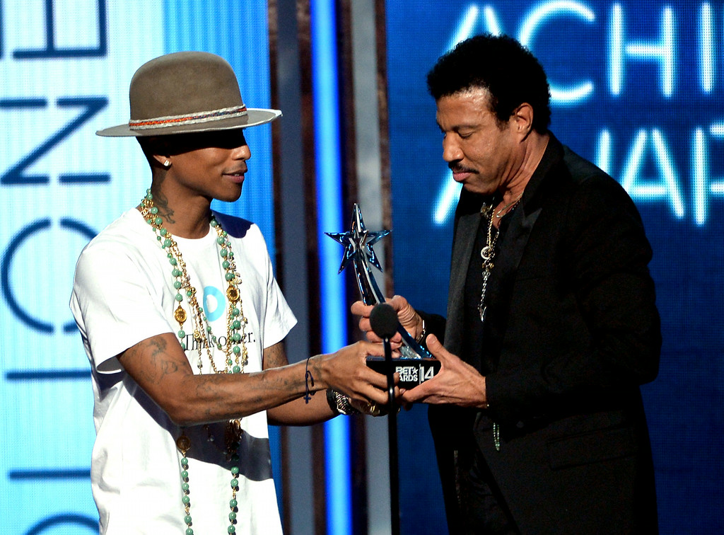 Description of . Singer Lionel Richie (R) accepts the 2014 BET Lifetime Achievement Award from singer Pharrell Williams onstage during the BET AWARDS '14 at Nokia Theatre L.A. LIVE on June 29, 2014 in Los Angeles, California.  (Photo by Kevin Winter/Getty Images for BET)