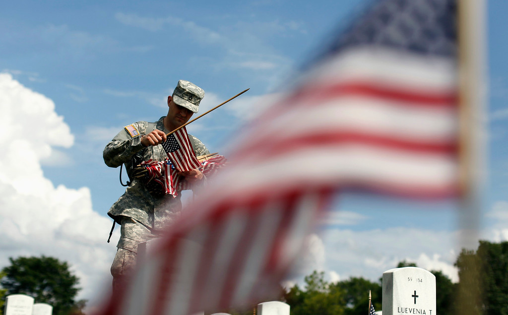 Description of . A soldier of the Third U.S. Infantry Regiment (The Old Guard) places a flag at a grave at Arlington National Cemetery in Virginia May 23, 2013. The annual