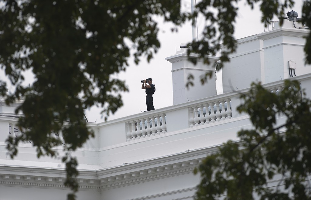 Description of . A member of the US Secret Service looks out toward Lafayette Park from the roof of the White House in Washington, DC, October 3, 2013, following reports of a shooting at the US Capitol. AFP PHOTO / Saul LOEB/AFP/Getty Images