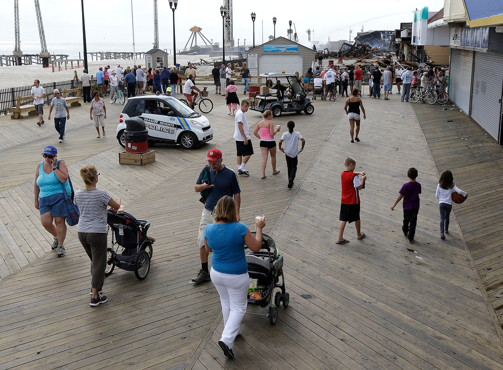 Description of . People walk on the operating side of the Seaside Park boardwalk near the area where a day earlier a massive fire burned a large portion of the boardwalk, Friday, Sept. 13, 2013, in Seaside Park, N.J. The fire, which apparently started in an ice cream shop and spread several blocks, hit the recently repaired boardwalk, which was damaged last year by Superstorm Sandy. There were no reports of any injuries. (AP Photo/Julio Cortez)