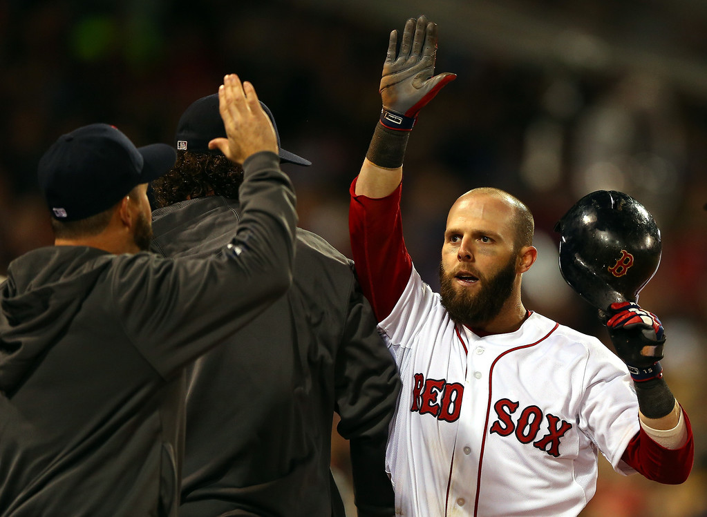 Description of . Dustin Pedroia #15 of the Boston Red Sox returns to the dugout after scoring in the first inning against the St. Louis Cardinals during Game One of the 2013 World Series at Fenway Park on October 23, 2013 in Boston, Massachusetts.  (Photo by Elsa/Getty Images)