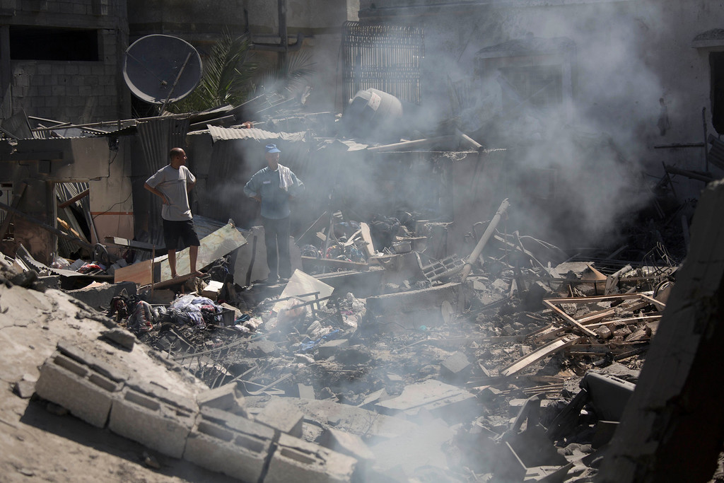 Description of . Palestinians inspect a destroyed house in the heavily bombed Gaza City neighborhood of Shijaiyah, close to the Israeli border, Friday, Aug. 1, 2014. A three-day Gaza cease-fire that began Friday quickly unraveled, with Israel and Hamas accusing each other of violating the truce. (AP Photo/Dusan Vranic)