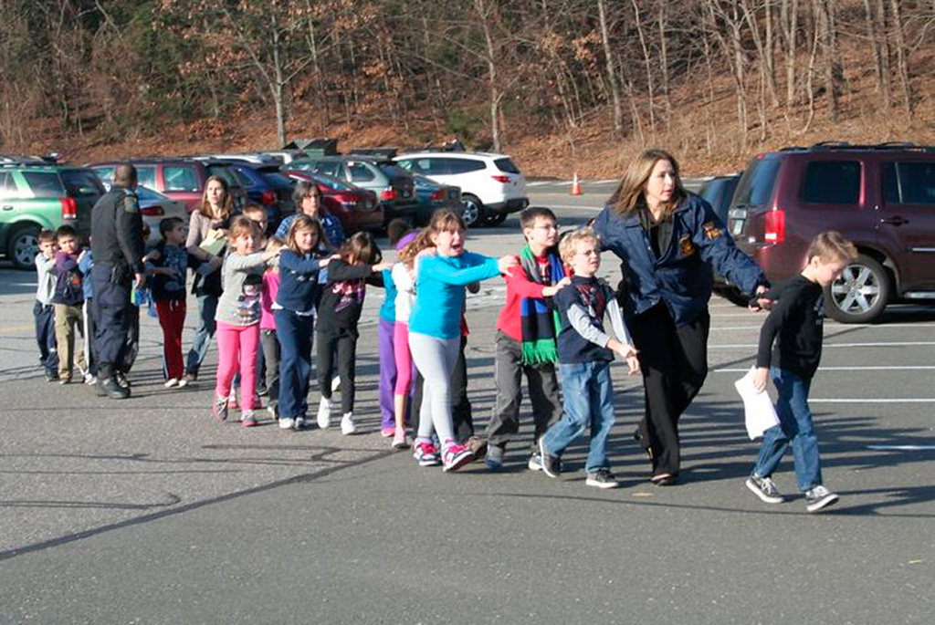 Description of . State police personnel lead children from the Sandy Hook Elementary School in this handout picture from the Newtown Bee, in Newtown, Connecticut, December 14, 2012. All public schools in Newtown, Connecticut, were placed in lockdown on Friday following a shooting at Sandy Hook Elementary School. REUTERS/Newtown Bee/Shannon Hicks/Handout