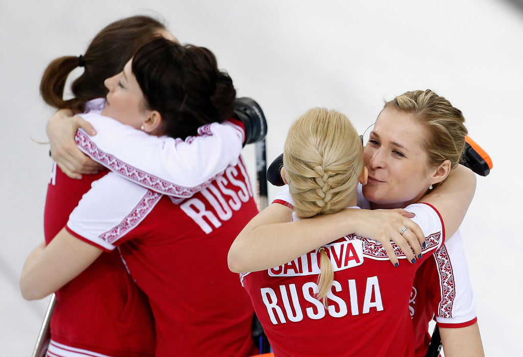 Description of . Russia\'s Margarita Fomina, far right, kisses teammate Alexandra Saitova, while skip Anna Sidorova and Ekaterina Galkin hug at left, after defeating the United States during women\'s curling competition at the 2014 Winter Olympics, Tuesday, Feb. 11, 2014, in Sochi, Russia. (AP Photo/Robert F. Bukaty)