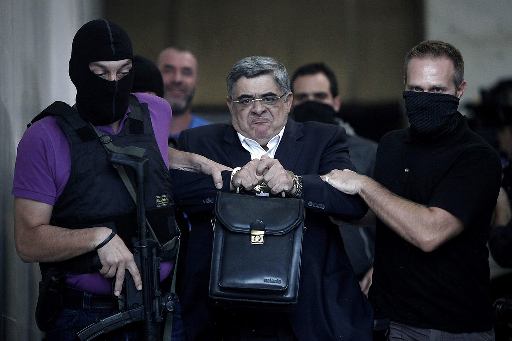 Description of . Leader of the ultra-right wing Golden Dawn party, Nikos Michaloliakos, is escorted by masked police officers to the prosecutor from the police headquarters in Athens on September 28, 2013. Greek police swooped on the neo-Nazi Golden Dawn party, hunting for dozens of members across the country in a crackdown sparked by the murder of a leftist musician.  ANGELOS TZORTZINIS/AFP/Getty Images