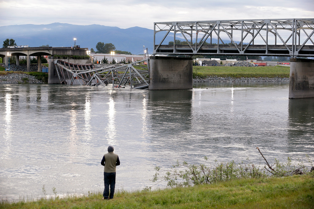 Description of . A person looks from the south bank of the Skagit River across to the collapsed portion of the Interstate 5 bridge Friday, May 24, 2013, in Mount Vernon, Wash. A truck carrying an oversize load struck the four-lane bridge on the major thoroughfare between Seattle and Canada, sending a section of the span and two vehicles into the Skagit River below Thursday evening. All three occupants suffered only minor injuries. At an overnight news conference, Washington State Patrol Chief John Batiste blamed the collapse on a tractor-trailer carrying a tall load that hit an upper part of the span. (AP Photo/Elaine Thompson)