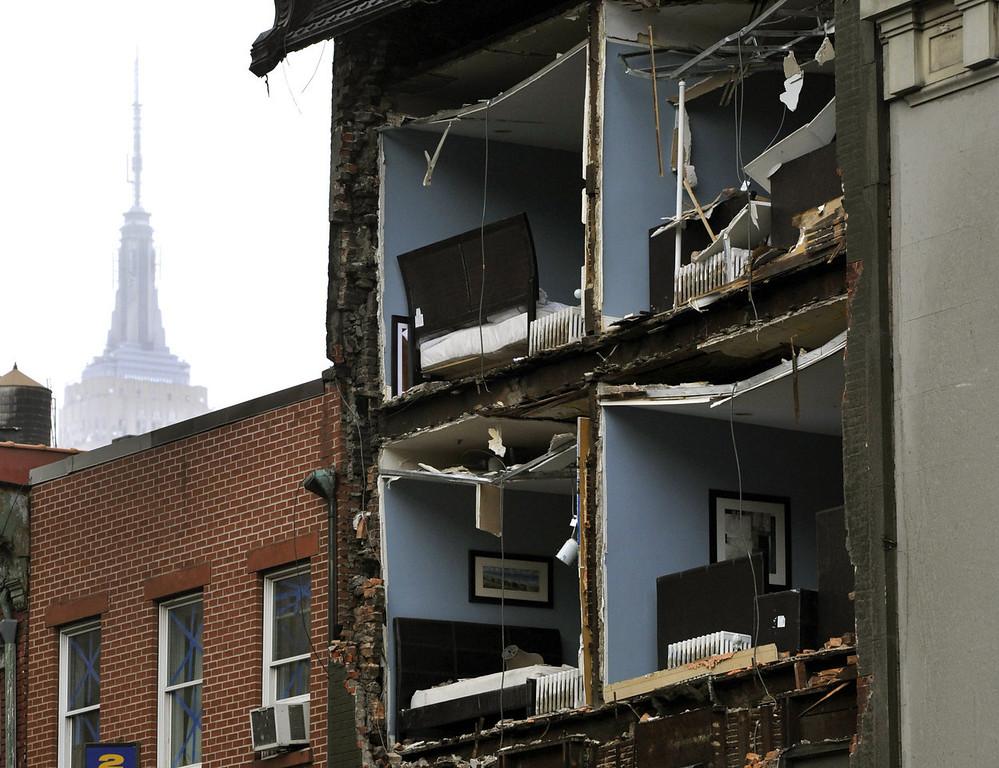 . The Empire State Building towers in the background of an apartment building in Chelsea, New York City, with the facade broken off October 30, 2012  the morning after Hurricane Sandy.  The death toll from superstorm Sandy has risen to 16 in the mainland United States and Canada, and was expected to climb further as several people were still missing, officials said Tuesday.  Connecticut, New York, New Jersey, Maryland, Pennsylvania, West Virginia and North Carolina reported 15 dead from the massive storm system, and Toronto police said a Canadian woman was killed by flying debris.   (Photo credit should read TIMOTHY A. CLARY/AFP/Getty Images)