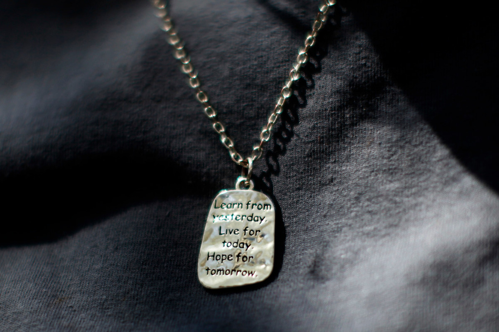 Description of . A woman wears a pendant inscribed with