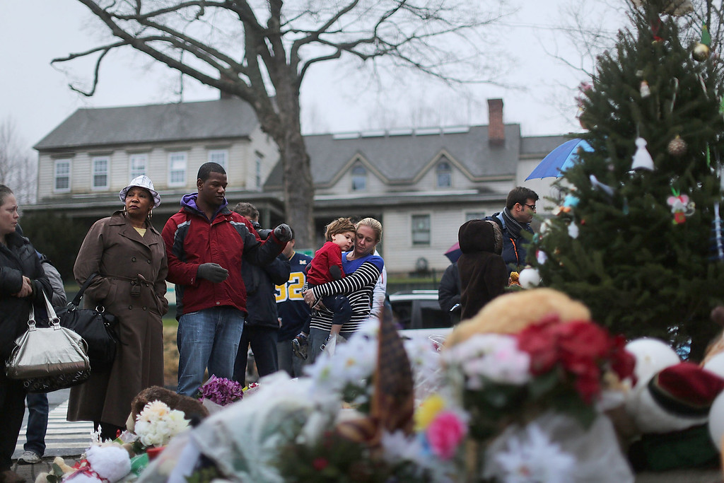 Description of . NEWTOWN, CT - DECEMBER 16:  People reflect at a memorial down the street from the Sandy Hook School December 16, 2012 in Newtown, Connecticut. Twenty-six people were shot dead, including twenty children, after a gunman identified as Adam Lanza opened fire at Sandy Hook Elementary School. Lanza also reportedly had committed suicide at the scene. A 28th person, believed to be Nancy Lanza, found dead in a house in town, was also believed to have been shot by Adam Lanza.  (Photo by Spencer Platt/Getty Images)