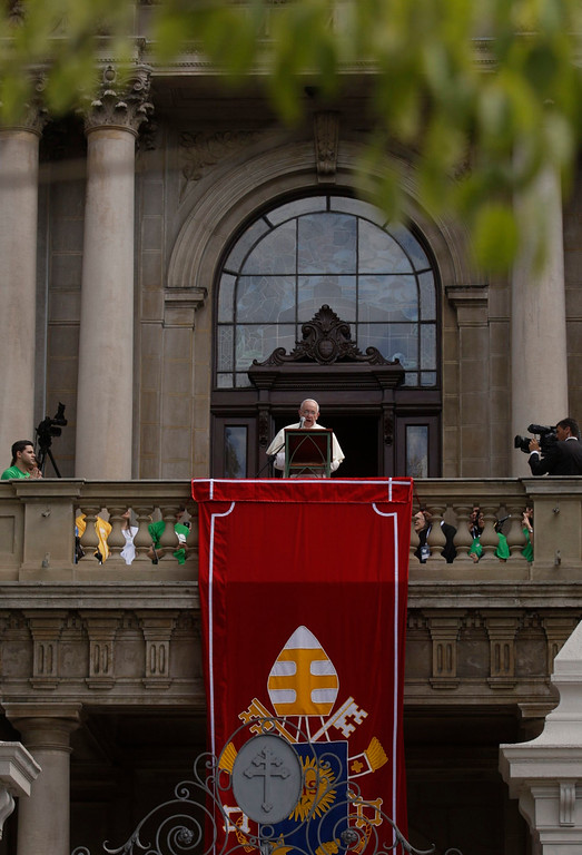 Description of . Pope Francis speaks from the balcony of Sao Joaquim Palace in Rio de Janeiro, July 26, 2013. Pope Francis on Thursday issued the first social manifesto of his young pontificate, telling slum dwellers in Brazil that the world's rich must do much more to wipe out vast inequalities between the haves and the have-nots.  REUTERS/Pilar Olivares