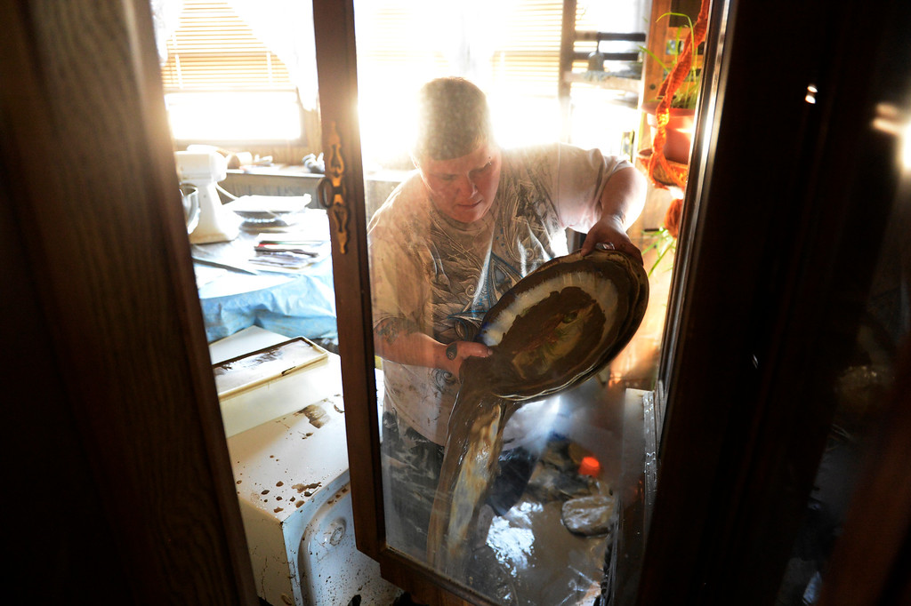 Description of . EVANS, CO - SEPTEMBER 17: Kathryn Reeves helps her elderly godparents in Evans carry out belongings from their flooded homes, September 17, 2013. Massive flooding continues to hit Colorado. (Photo By RJ Sangosti/The Denver Post)