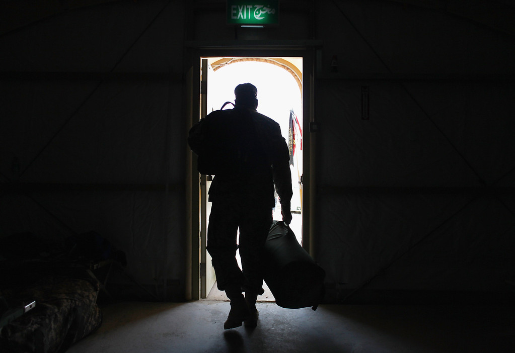 . U.S. Army Sergeant Quasim Singleton from Philadelphia, Pennsylvania of the 2-82 Field Artillery, 3rd Brigade, 1st Cavalry Division, carries his gear out of his temporary housing to a staging area as he waits to fly home from Kuwait after their unit exited from Iraq on December 15, 2011 at Camp Virginia, near Kuwait City, Kuwait. (Photo by Joe Raedle/Getty Images)